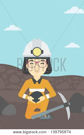 An asian female miner  in hard hat sitting with coal in hands and a pickaxe on the background of coal mine. Vector flat design illustration. Vertical layout.