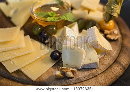 Wooden board with cheese in assortment, honey and fruit on black
