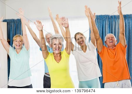 Instructor doing exercises with seniors during sports class