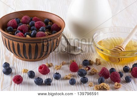 Muesli with fresh berries honey and milk on wooden background.