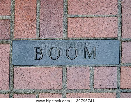 The word Boom engraved into a brick on the floor
