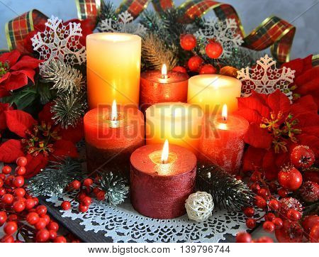 Festive burning candles with traditional Christmas decorations, conifer branches, berries and baubles on plate with white napkin. Christmas and New Year celebratory still life.