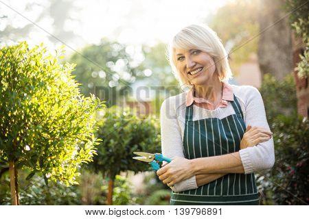 Portrait of confident female gardener standing by plants
