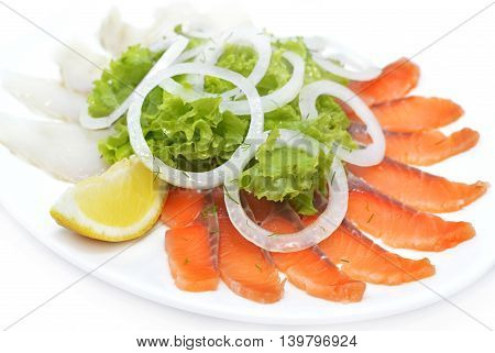 White and red salted fish with greenery and lemon