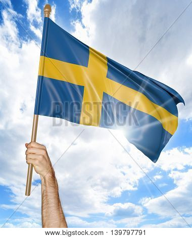 Person's hand holding the Swedish national flag and waving it in the sky, 3D rendering