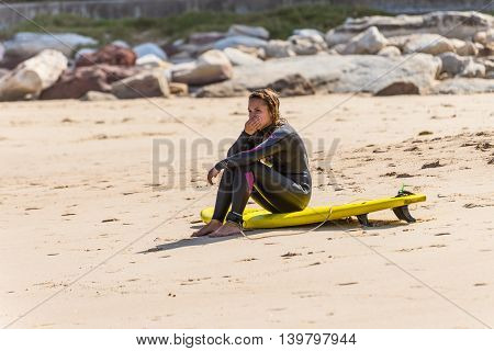 Sydney Australia - November 26 2014: Girl with her surfboard sitting on the beach Bondi Beach in the Eastern Suburbs Sydney New South Wales Australia.