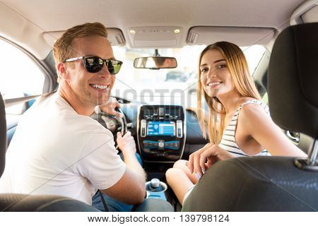 Make yourself comfortable. Smiling ecstatic man and beautiful young woman sitting in the car and looking at the back seats