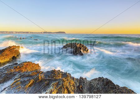 Clear skies sunrise with waves lashing against a rock in the ocean, at Currumbin Rock Gold Coast