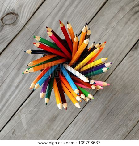 Colored pencils background. Set of colored pencils in the holder on wooden background top view