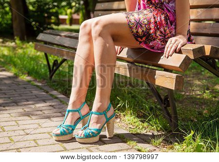 young girl in green shoes sitting on a park bench on sunny summer day. legs closeup