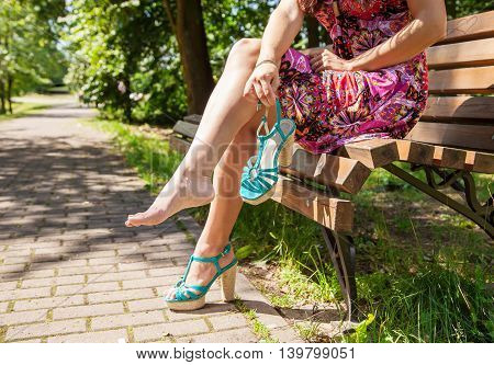 young woman holding a shoe sitting on a park bench. legs closeup