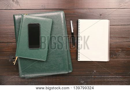 On the Office Desk Is Open Notebook With Blank Pages Pen Leather Business Folder And Smartphone With Blank Screen. Top view
