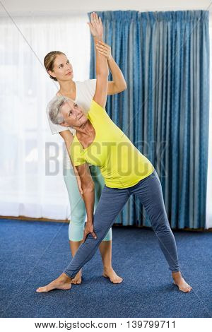 Instructor helping senior woman with sport exercises during sports class