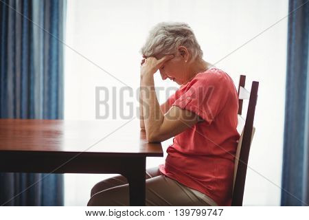 Sad senior woman sitting at a table in a retirement home