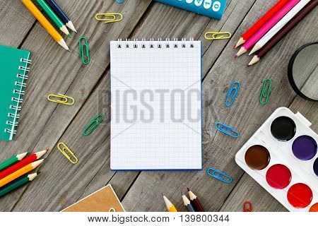 Open notebook with school different supplies on gray wooden table top view