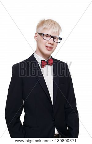 Albino young man portrait. Blond guy in suit with red bow tie isolated at white background. Albinism, pale skin. Stylish young boy in eye glasses and suit.
