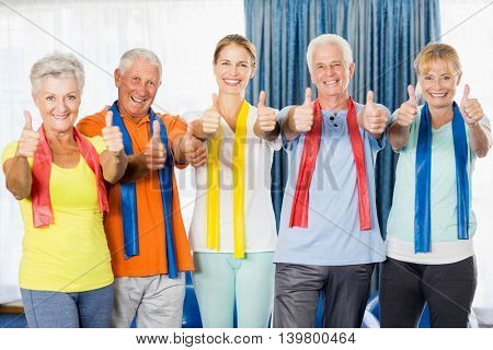 Instructor and seniors with thumbs up during sports class
