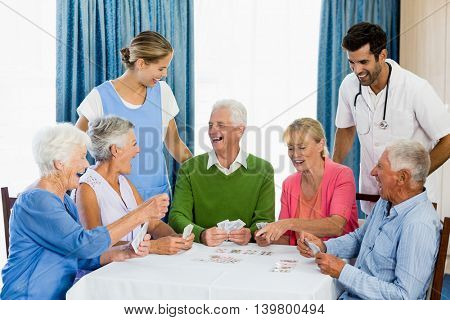 Seniors playing cards in a retirement home