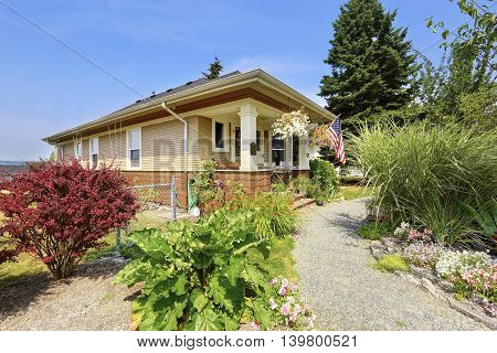 View Of American Craftsman House With Lots Of Greenery In The Front.
