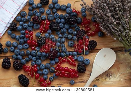 Mix of fresh berries with dry lavender and wooden spoon