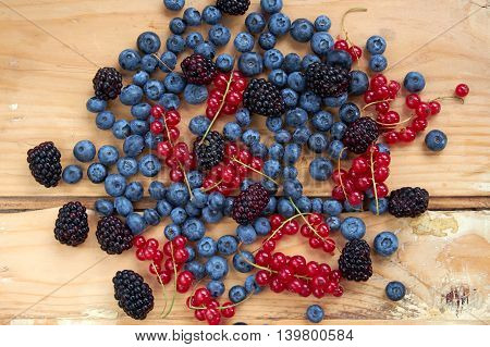 Blueberry red currant and blackberry mix on wooden background