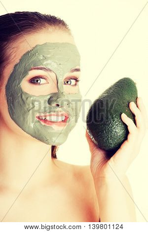 Beautiful woman with green avocado clay facial mask