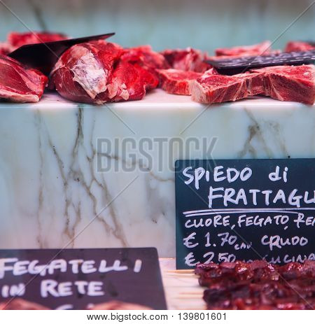 Close up of various Meats in the butchery - Translation italian words from left: Little livers inside the net offal skewer heart liver uncooked