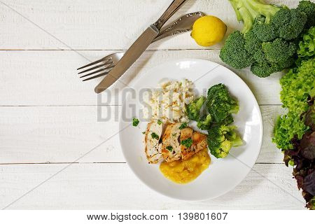 fried chicken breast fillet with a fruity sauce broccoli and rice and the ingredients on a white painted wooden background top view from above generous copy space