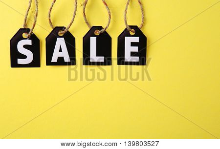Black paper tags with strings on yellow background. Sale concept