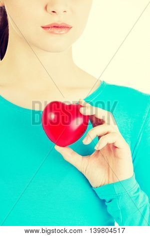 Attractive woman holding a heart, closeup.