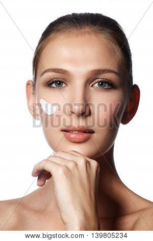 Beautiful face of young woman with cosmetic cream on a cheek. Skin care concept. Closeup portrait isolated on white. Close-up young beautiful face of girl applying moisturize cream