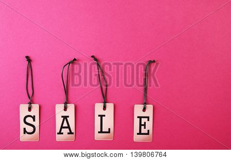 Paper tags with strings on pink background. Sale concept