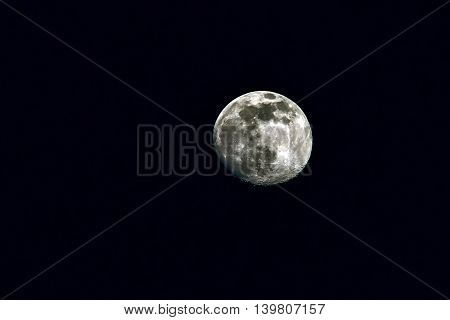 Closeup of the full moon on the black sky.