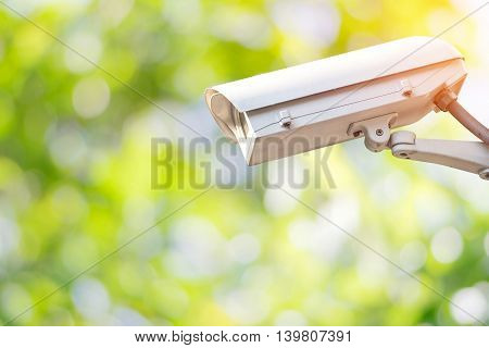 Closeup CCTV or surveillance camera in the garden with colorful green nature background.