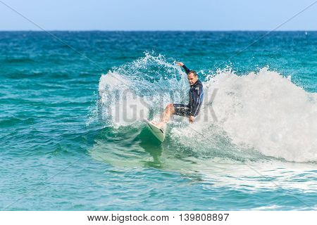 Sydney Australia - November 26 2014: A man rides his surfboard towards the shore. Famous Bondi Beach offers a wide range of sports and recreational activities.