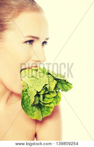 Caucasian topless woman with lettuce in mouth.