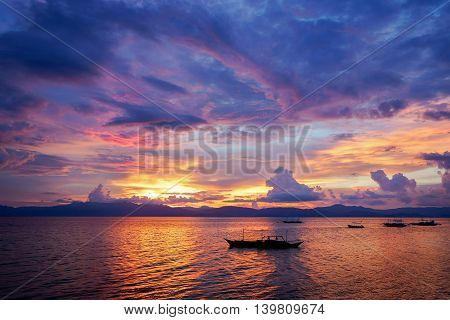 Amazing colorfull sunset at the sea with philippine boat in Moalboal