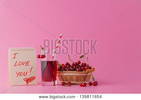 Sweet Cherries In A Basket And Glass Juice On  Pink Background