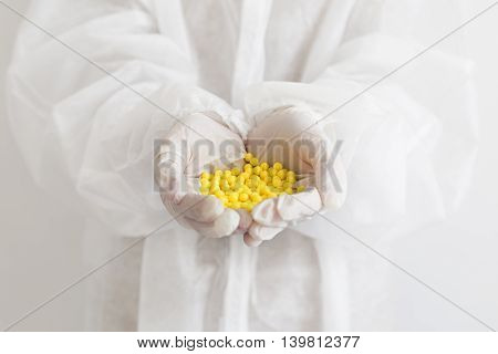 Close up photo of hands holding yellow pills. Vitamins in hands concept