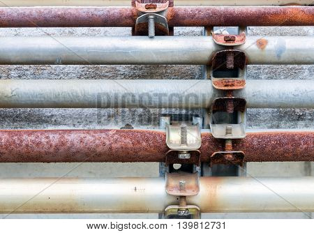Dirty pipeline set with the metal screw on the facoty wall.