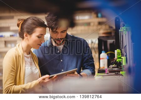 Graphic designers interacting using digital tablet in office