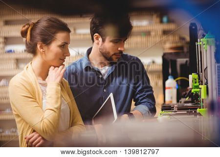 Graphic designers holding digital tablet looking at a model in office