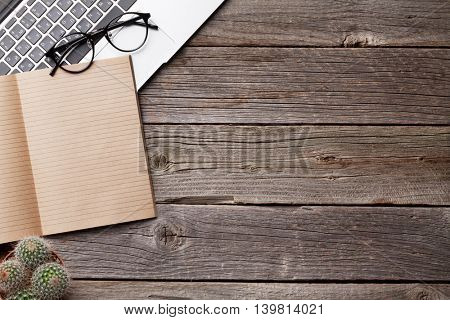 Notepad for your text, glasses and laptop over wooden table. Top view with copy space