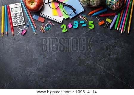 Supplies and apple over chalk board for your text. Back to school concept with copy space
