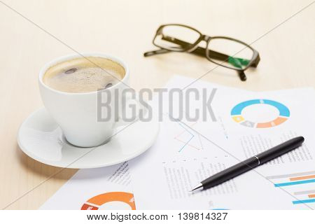 Office workplace with coffee cup, supplies and reports on wood desk table