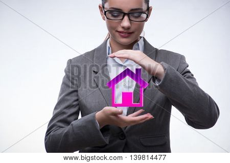 Young businesswoman holding house in real estate concept