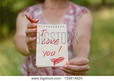 Hand Holding White Heart Paper With I Love You Text On Blur Green Grass Background
