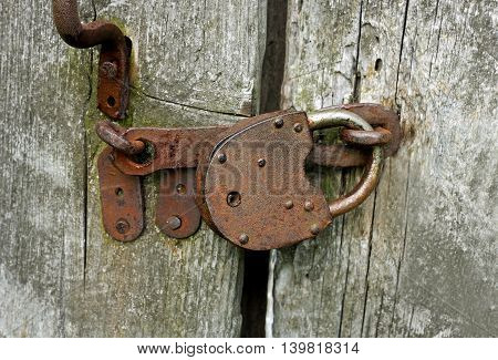 Old rusty lock hanging on the wooden door.