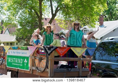 WEST ST. PAUL, MINNESOTA - MAY 21, 2016: West Wind organization promoting Saint Paul Winter Carnival waves to crowd from motorcade during annual West St. Paul Days Grande Parade on May 21.