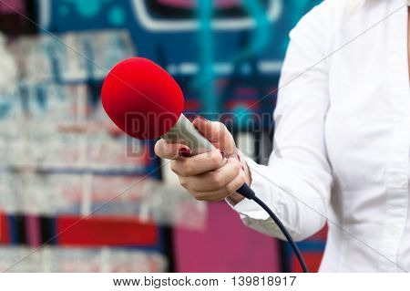Female reporter at news conference holding red microphone